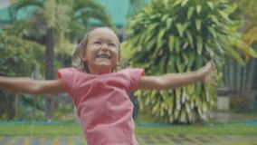 Portrait 5 year old child girl having fun during a tropical rain, slow motion. Portrait 5 year old child girl having fun during a tropical rain in slow motion stock video