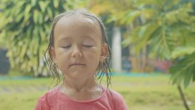 Portrait 5 year old child girl looking at camera during a tropical rain. In slow motion stock video footage