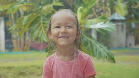 Portrait 5 year old child girl looking at camera during a tropical rain. In slow motion stock footage