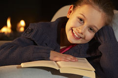 Portrait 7 year old girl reading by firelight Royalty Free Stock Images