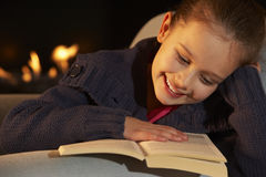 Portrait 7 year old girl reading by firelight Royalty Free Stock Photos
