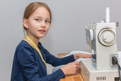 Girl sewing a pink and white striped cloth with a sewing machine royalty free stock photography