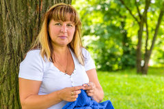 Portrait of 50-year-old woman engaged in knitting Stock Image