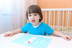 Portrait of 2 years boy making snowman of cotton pad Royalty Free Stock Images