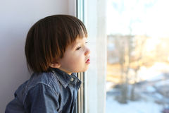 Portrait of 2 years boy sits on sill and looks out of window in Royalty Free Stock Image