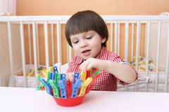Portrait of 2 years child playing with clothes pins Royalty Free Stock Images