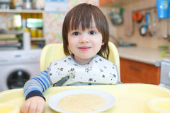 Portrait of 2 years little child eating wheat porridge with pump Stock Image