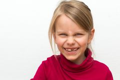 Portrait of a 6 years old blond girl. It wears a red turtleneck stock image
