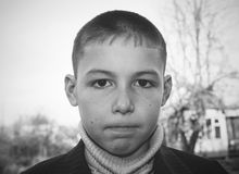 Portrait of 8 years old boy with serious face and tightly clenched lips. Black and white photo Royalty Free Stock Photos