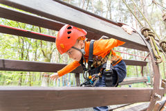 Portrait of 3 years old boy wearing helmet and climbing. Child in a wooden abstacle course in adventure playground Royalty Free Stock Image