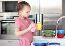 Little girl washing the dishes. Portrait of a 6 years old girl washing the dishes at home Royalty Free Stock Photography