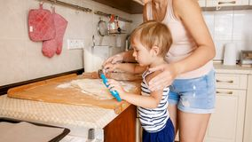 Portrait of cute 3 years old toddler boy cooking cookies with mother. Family cooking and baking. Portrait of 3 years old toddler boy cooking cookies with mother royalty free stock photos