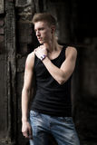 Portrait yog young man in shirt and jeans standing on abandoned background. Royalty Free Stock Photos