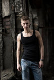 Portrait yog young man in shirt and jeans standing on abandoned background. Stock Photography