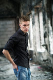 Portrait yog young man in shirt and jeans standing on abandoned background. Young man in shirt and jeans standing on abandoned background Royalty Free Stock Photo