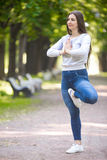 Portrait of yogi woman standing in Vrikshasana pose. Portrait of smiling beautiful sporty young woman working out in park alley, doing stretching exercise Stock Image