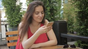 The portrait of youg lady typing messeges on her smartphone sitting in cozy street cafe. The female in pink dress enjoys her communication and smiles looking stock video