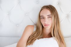 Portrait of yound sad woman lying on bed in light room, loss of appetite.  royalty free stock images