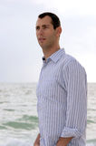 Portrait of younf man at ocean looking left. Three quarter profile portrait of man in his late twenties, looking to the left, shot outdoors under cloudy sky Royalty Free Stock Photos