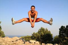 Portrait of young. A young man makes a leap in the mountains of Crimea on the mountain cat Royalty Free Stock Photo