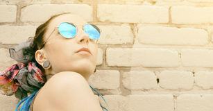 Portrait young active girl of the hipster outdoors in sunglasses Stock Photo