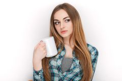 Portrait of a young adorable blonde woman in blue plaid shirt enjoying her warm cozy drink in big blank white mug. Portrait of a young adorable blonde lady in Stock Photography