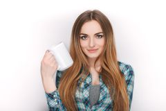 Portrait of a young adorable blonde woman in blue plaid shirt enjoying her warm cozy drink in big blank white mug. Royalty Free Stock Photography