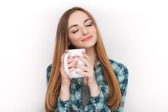 Portrait of a young adorable blonde woman in blue plaid shirt enjoying her warm cozy drink in big blank white mug. Stock Image