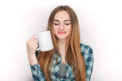 Portrait of a young adorable blonde woman in blue plaid shirt enjoying her warm cozy drink in big blank white mug. Royalty Free Stock Photos