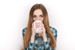 Portrait of a young adorable blonde woman in blue plaid shirt enjoying her warm cozy drink in big blank white mug. Stock Images