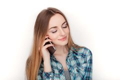 Portrait of a young adorable blonde woman in blue plaid shirt enjoying having emotional conversation on smartphone. Stock Images