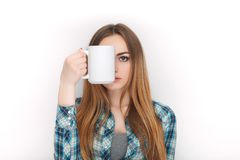 Portrait of a young adorable blonde woman in blue plaid shirt enjoying her warm cozy drink in big blank white mug. Portrait of a young adorable blonde lady in Royalty Free Stock Image
