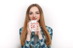 Portrait of a young adorable blonde woman in blue plaid shirt enjoying her warm cozy drink in big blank white mug. Portrait of a young adorable blonde lady in Stock Image
