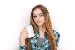 Portrait of a young adorable blonde woman in blue plaid shirt enjoying her warm cozy drink in big blank white mug. Royalty Free Stock Photo