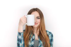 Portrait of a young adorable blonde woman in blue plaid shirt enjoying her warm cozy drink in big blank white mug. Royalty Free Stock Image