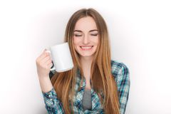 Portrait of a young adorable blonde woman in blue plaid shirt enjoying her warm cozy drink in big blank white mug. Portrait of a young adorable blonde lady in Stock Photos