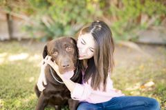 Attractive woman and dog cuddle. Portrait of a young adorable woman in pink shirt and blue jeans sitting in park hugging pet dog Royalty Free Stock Image