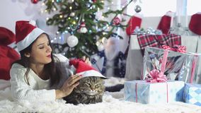 Portrait of young adorable woman sitting beside Christmas tree at home wearing Christmas cap playing with Maine Coon cat