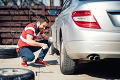 Portrait of young adult changing tires for season change. Portrait of young man changing tires for season change Stock Image