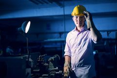 Portrait of young adult experienced industrial asian worker over industry machinery. Production line manufacturing workshop royalty free stock photos