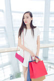 Portrait young adult girl with colored bags Stock Images