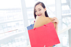 Portrait young adult girl with colored bags Royalty Free Stock Images