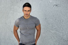 Portrait of young adult handsome man wearing grey casual t-shirt and posing near grey wall. Stock Images