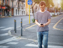 Portrait of young adult man crossing inattentively the street di Royalty Free Stock Photo