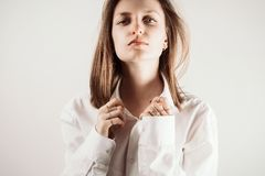 Portrait of young adult woman with eyes closed holding collar of white shirt. With her hands, selective focus royalty free stock photography
