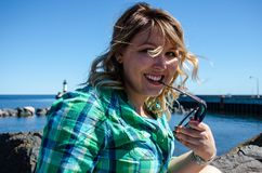 Portrait of a young adult woman with sunglasses, looking coy, at. Canal Park in Duluth Minnesota. Lighthouse blurred in background royalty free stock images