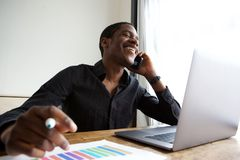 Young african american business man sitting at desk with laptop talking on cellphone. Portrait of young african american business man sitting at desk with laptop Royalty Free Stock Photos