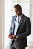 Portrait of a young African American business man using a mobile Stock Photography