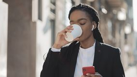 Portrait of a young African American businesswoman in a suit, standing on the old city background, drinking coffee and stock video footage