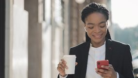 Portrait of a young African American businesswoman in a suit, walking around the city, drinking coffee and using stock video